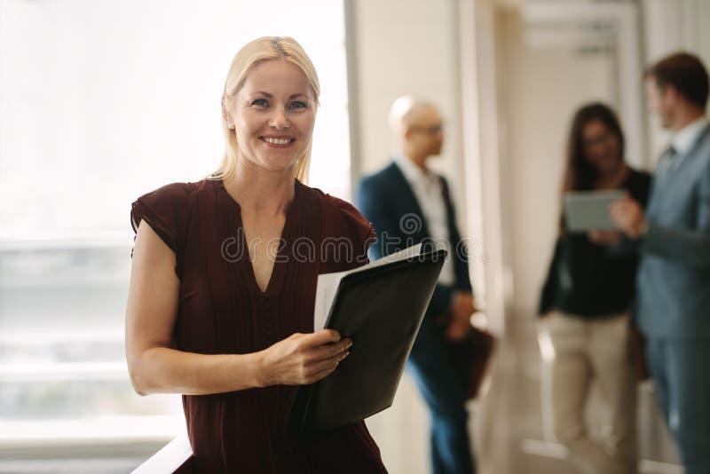 Kvinnlig chef med kollegor baktill arkivfoton