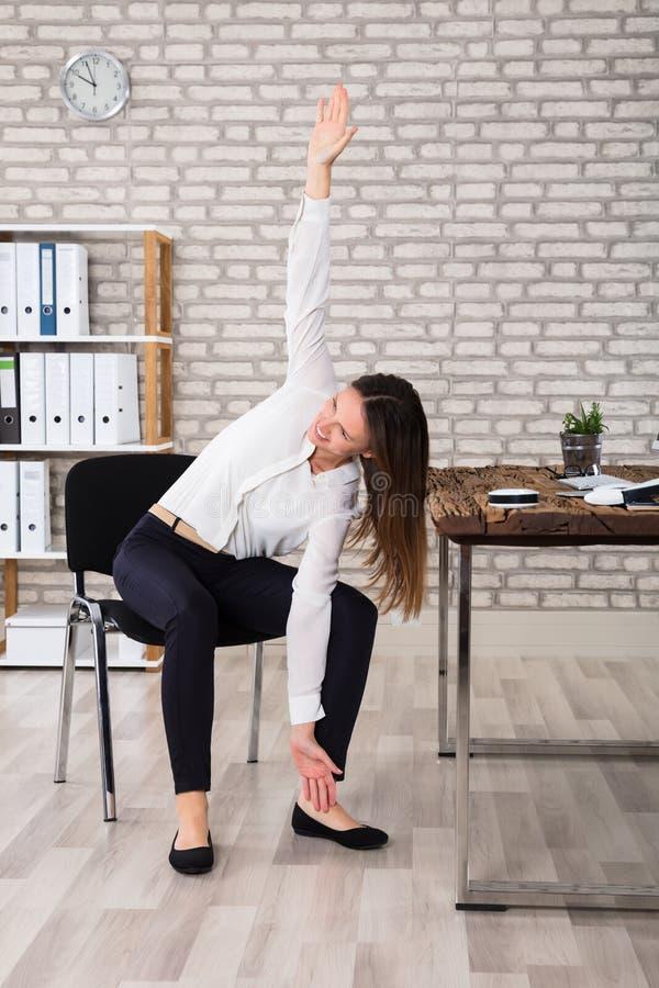 Kvinnlig chef Stretching Her Arms royaltyfri foto