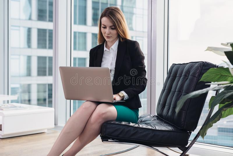 Kvinnlig chefsekonom som analyserar data genom att använda bärbar datorsammanträde på fåtöljen i modernt kontor arkivfoto