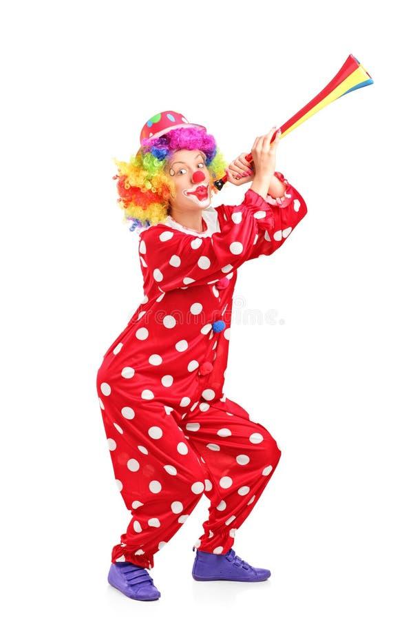 Kvinnlig clown som blåser ett horn arkivfoto