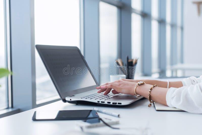 Kvinnlig copywriter på hennes arbetsplats, hem och att skriva ny text genom att använda bärbara datorn och internetuppkoppling Wi arkivbild