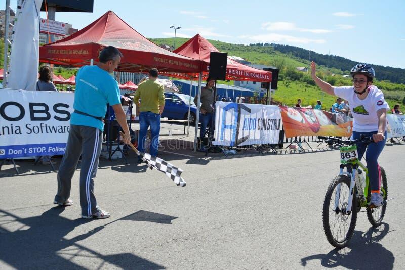 Kvinnlig cykelryttare på mållinjen fotografering för bildbyråer