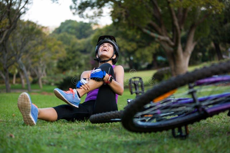 Kvinnlig cyklist som får sårad, medan falla från mountainbiket royaltyfri foto