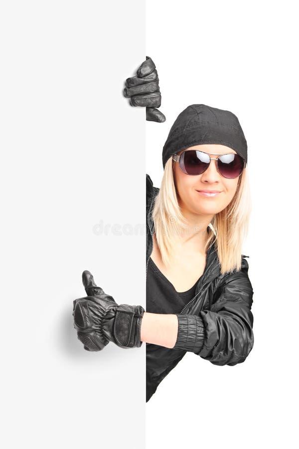 Kvinnlig cyklist som ger tummen upp bak en panel arkivfoto