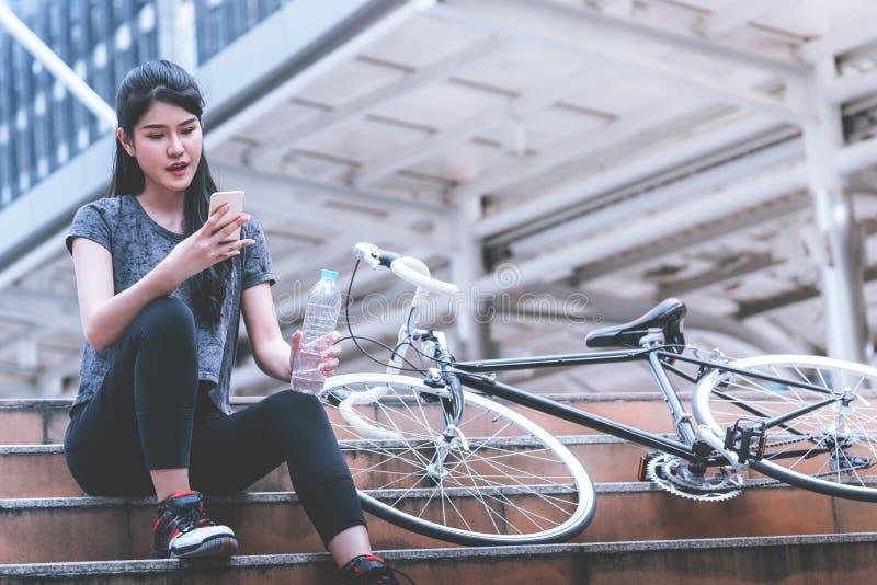 Kvinnlig cyklist som kopplar av dricksvatten på en trappa arkivbilder