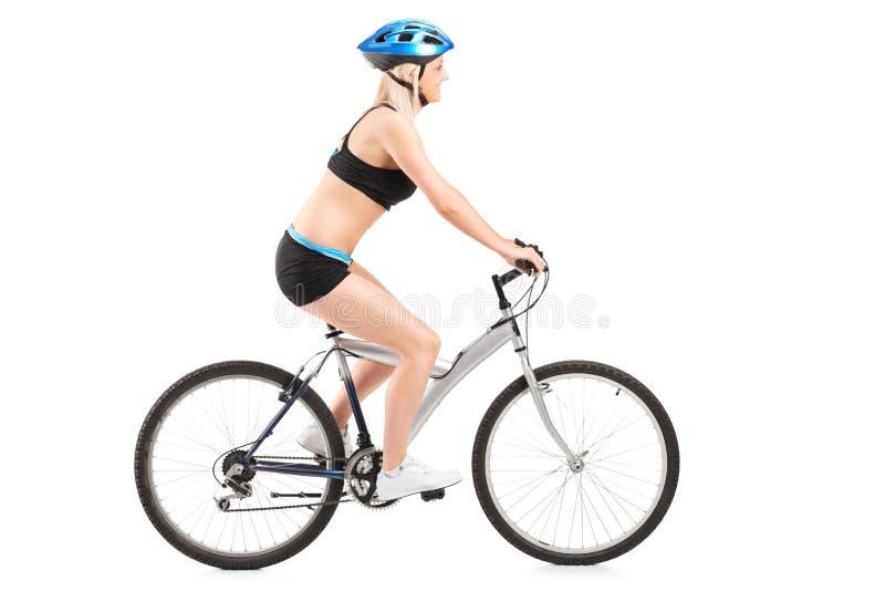 Kvinnlig cyklist som rider en cykel arkivfoton