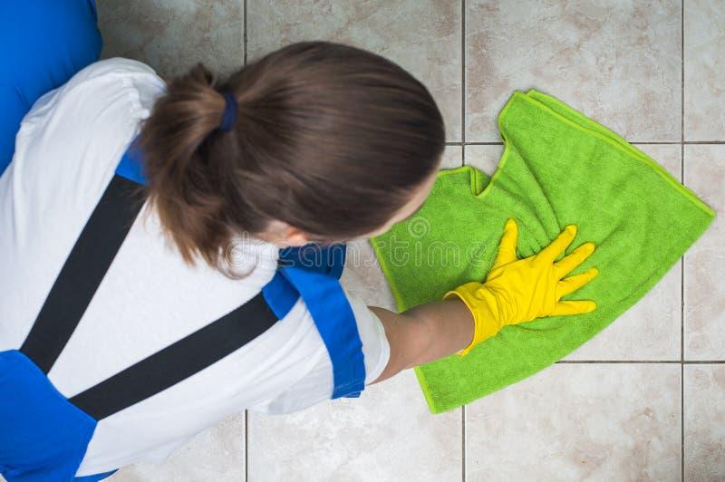 Kvinnlig dörrvakt i workwearlokalvårdgolv royaltyfri foto