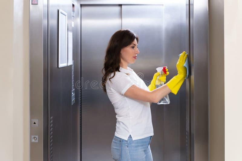 Kvinnlig d?rrvaktCleaning Elevator With dammtrasa royaltyfri fotografi