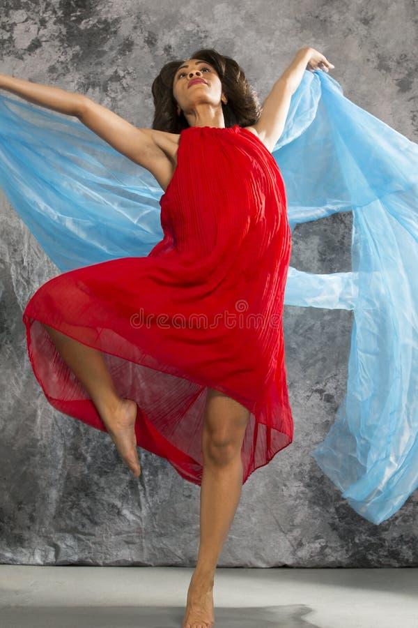 Kvinnlig dansare med virvlande runt blå tyg- och grå färgbakgrund royaltyfria bilder