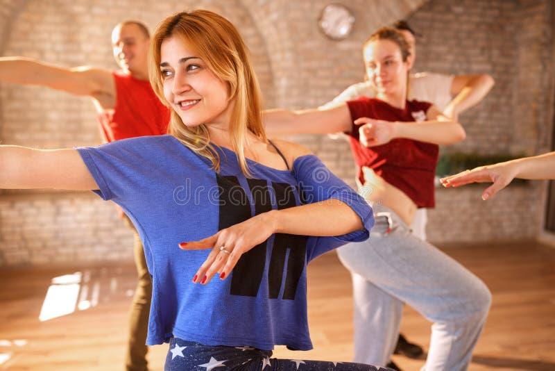 Kvinnlig dansaredans med gruppen royaltyfri fotografi