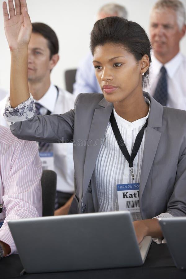 Kvinnlig delegat som lyssnar till presentationen på konferensdanandeanmärkningar på bärbara datorn royaltyfria foton