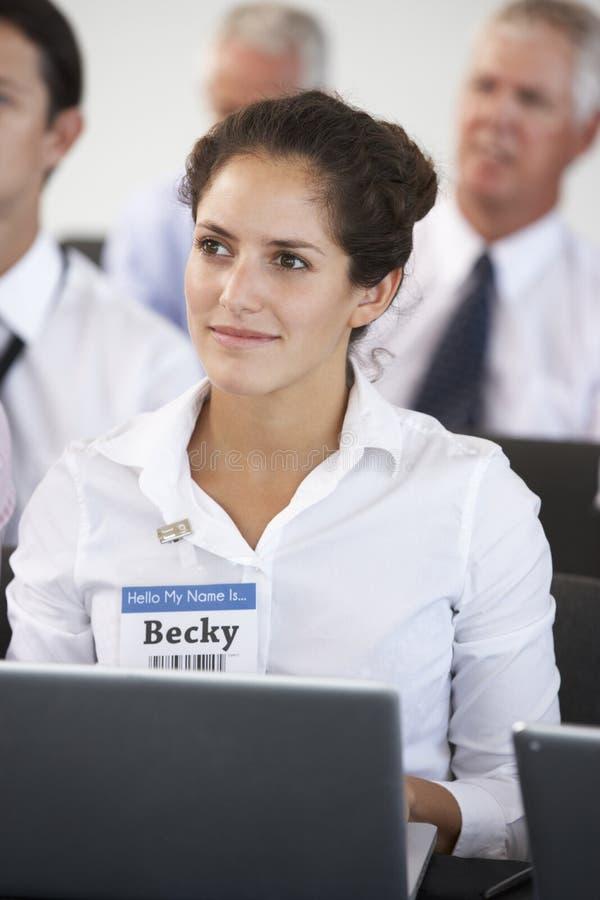 Kvinnlig delegat som lyssnar till presentationen på konferensdanandeanmärkningar på bärbara datorn arkivbilder