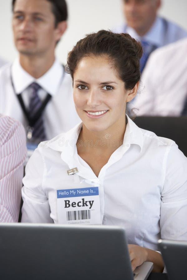 Kvinnlig delegat som lyssnar till presentationen på konferensdanandeanmärkningar på bärbara datorn royaltyfri fotografi