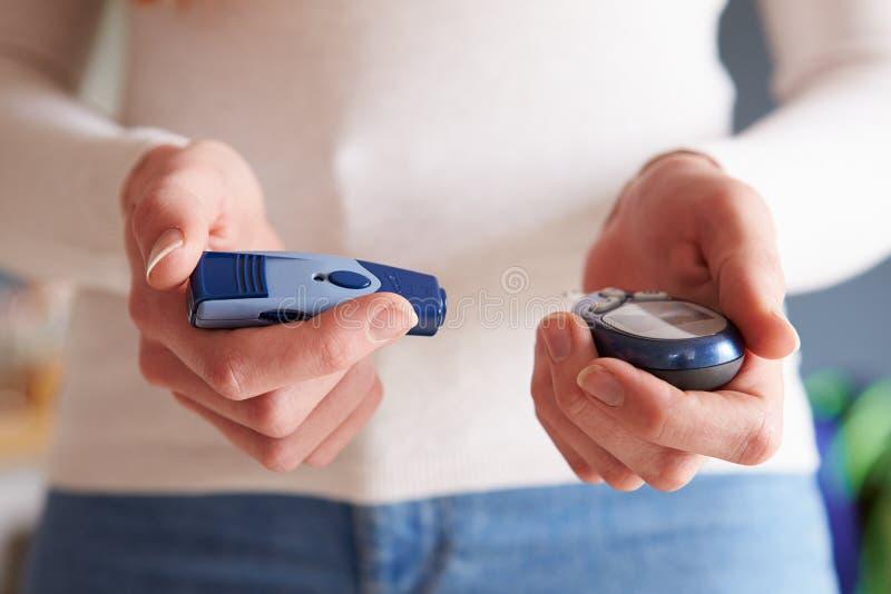Kvinnlig diabetiker som kontrollerar blod Sugar Levels royaltyfri foto