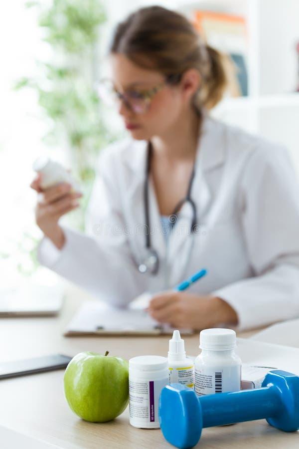 Kvinnlig dietist som rymmer ett näringsrikt tillägg, medan skriva rekvisitan i konsultationen royaltyfri fotografi