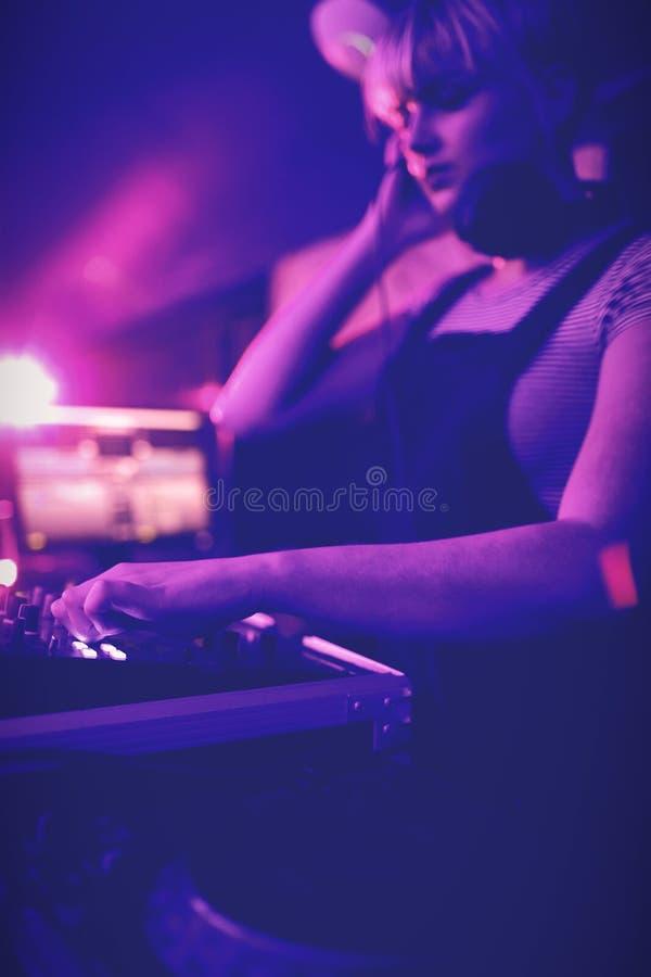 Kvinnlig dj som lyssnar till hörlurar, medan spela musik royaltyfri bild