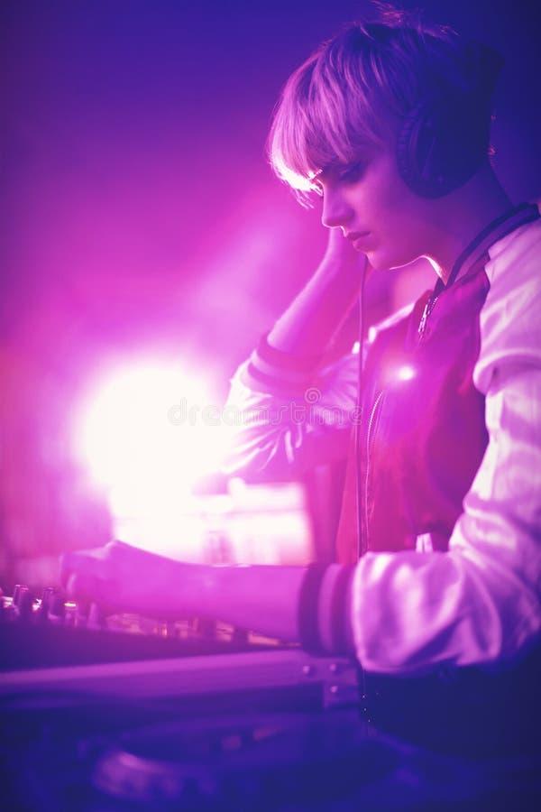 Kvinnlig dj som lyssnar till hörlurar, medan spela musik royaltyfria bilder