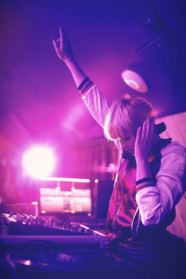 Kvinnlig dj som vinkar hennes hand, medan spela musik i stång arkivfoton