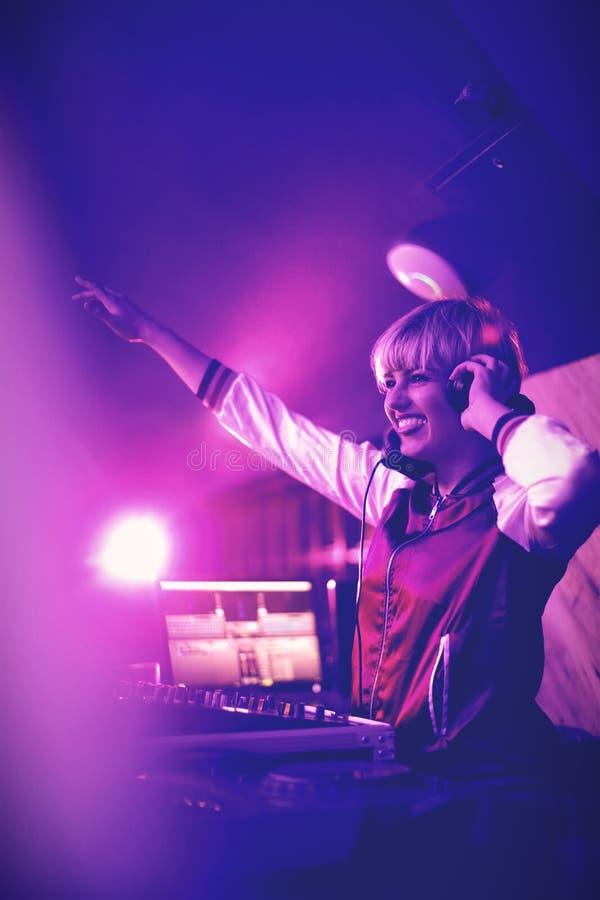 Kvinnlig dj som vinkar hennes hand, medan spela musik i stång fotografering för bildbyråer