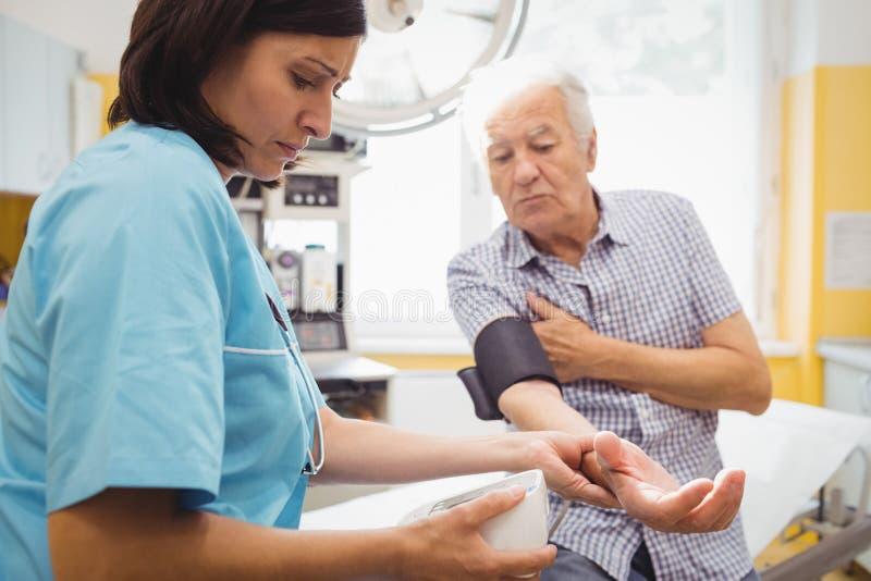 Kvinnlig doktor Checking Blood Pressure av tålmodign fotografering för bildbyråer