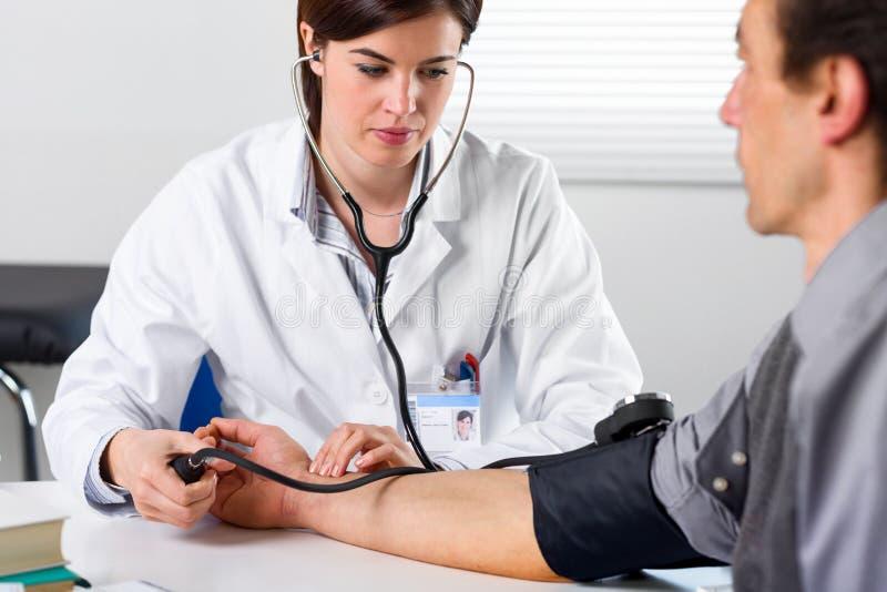 Kvinnlig doktor Checking Blood Pressure av tålmodign royaltyfria foton