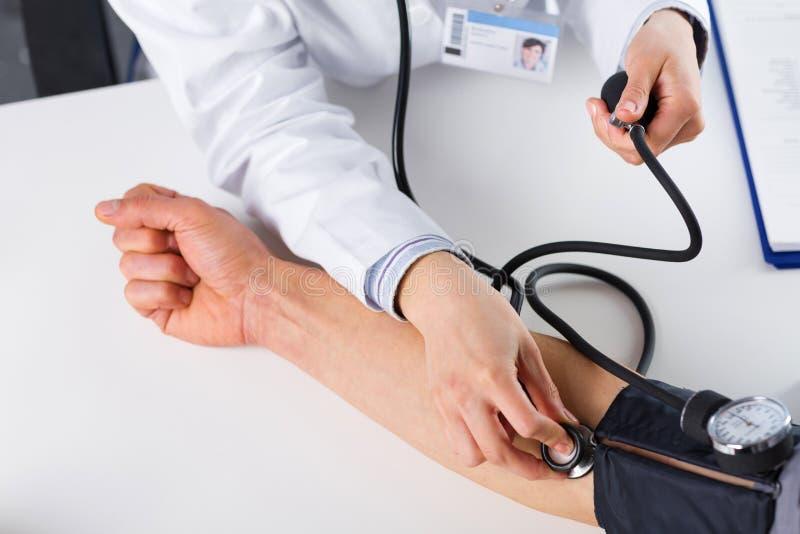 Kvinnlig doktor Checking Blood Pressure av tålmodign royaltyfri bild