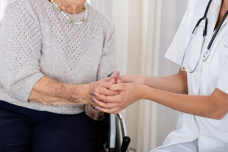 Kvinnlig doktor Consoling Senior Patient royaltyfria foton