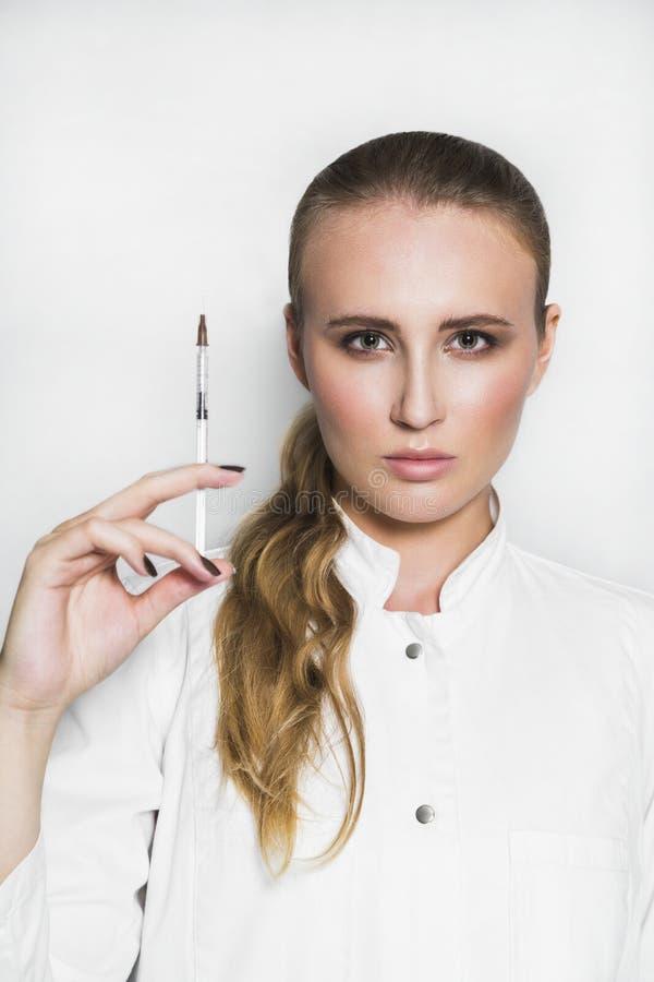Kvinnlig doktor eller forskare i medicinsk kappa med injektionssprutan på vit bakgrund royaltyfria bilder
