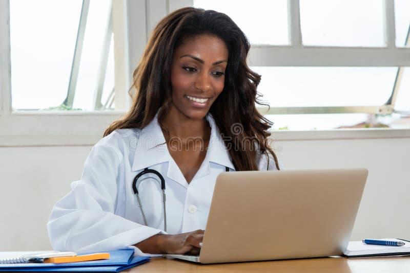 Kvinnlig doktor för afrikansk amerikan på datoren royaltyfria bilder