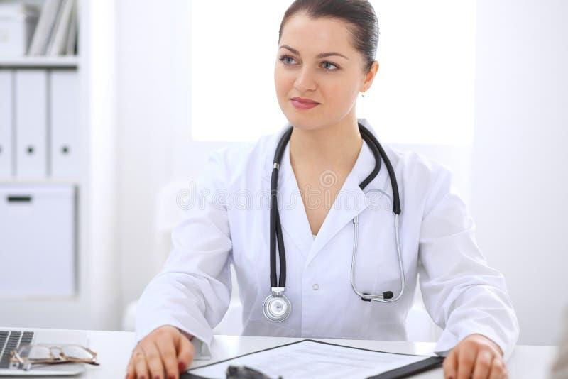 Kvinnlig doktor för brunett som talar till patienten på sjukhuskontoret Läkaren säger om resultat för medicinska examina för att  royaltyfri bild