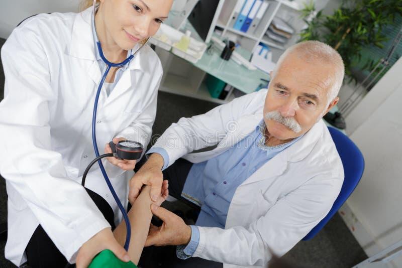 Kvinnlig doktor för internist som tar patienter blodtryck under bevakning arkivbild