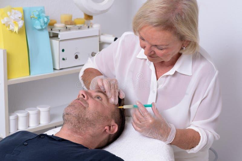 Kvinnlig doktor Giving Injection till patienten royaltyfria bilder