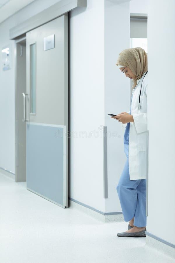 Kvinnlig doktor i hijab genom att använda mobiltelefonen på korridoren royaltyfri bild
