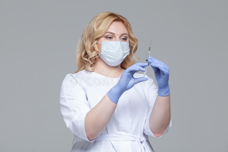 Kvinnlig doktor i injektionsspruta f?r innehav f?r framsidamaskering St?ende av doktorn eller sjuksk?terskan f?r ung kvinna i sky arkivbilder