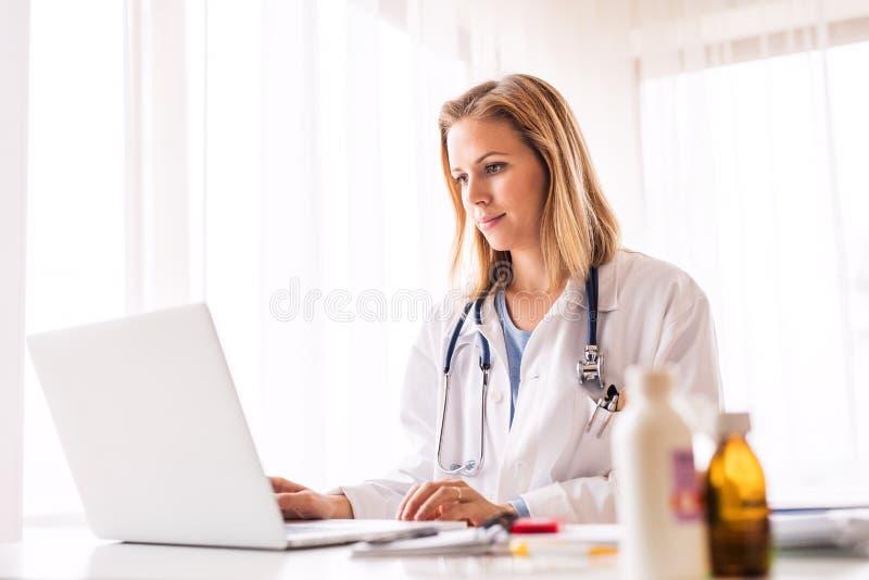 Kvinnlig doktor med bärbara datorn som arbetar på kontorsskrivbordet arkivbilder