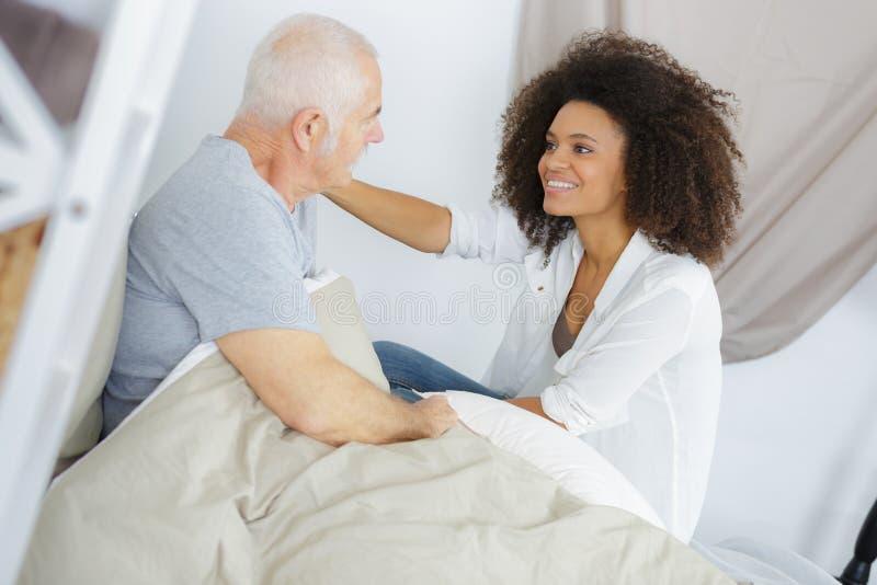 Kvinnlig doktor med den höga manliga patienten som ligger i säng royaltyfria bilder