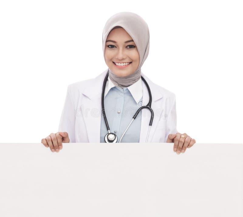 Kvinnlig doktor med det vita brädet för stetoskopinnehavmellanrum som isoleras på vit bakgrund arkivfoto