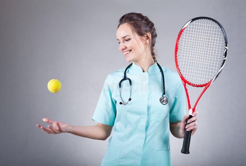 Kvinnlig doktor med en tennisracket royaltyfria bilder