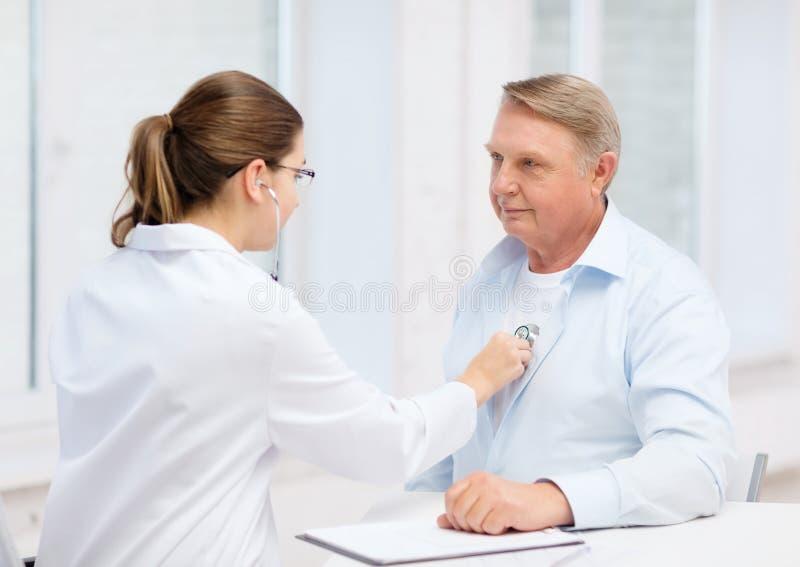 Kvinnlig doktor med gamala mannen som lyssnar till hjärtatakten arkivfoton