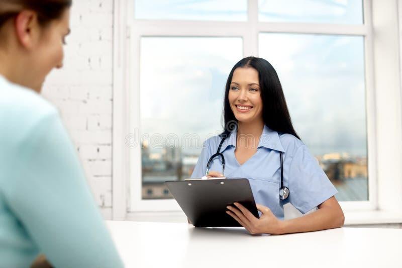 Kvinnlig doktor med skrivplattan och patienten på kliniken royaltyfria foton
