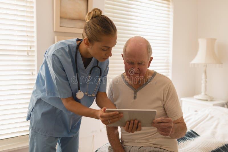 Kvinnlig doktor och hög man som använder den digitala minnestavlan arkivbild
