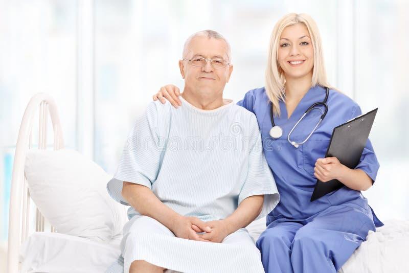Kvinnlig doktor och mogen en patient som placeras på säng royaltyfri fotografi