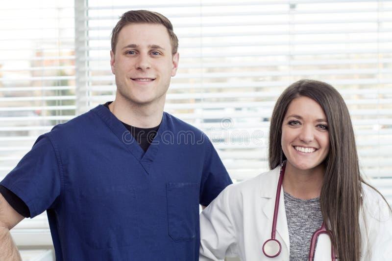 Kvinnlig doktor och sjukskötare som i regeringsställning ler arkivfoto