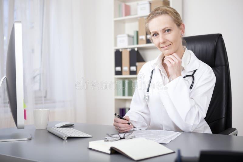 Kvinnlig doktor på hennes tabell med pennan och papper arkivfoto