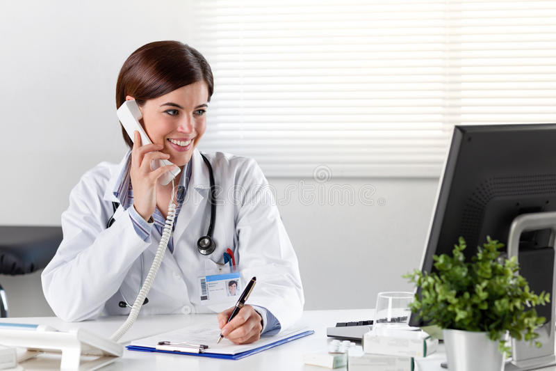 Kvinnlig doktor på skrivbordet med telefonen royaltyfria foton
