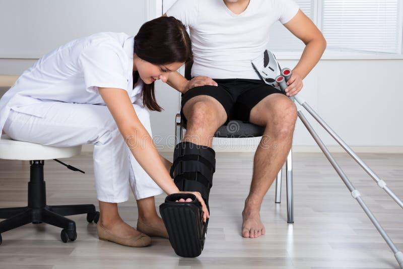 Kvinnlig doktor Putting Walking Brace på benet för person` s royaltyfria bilder