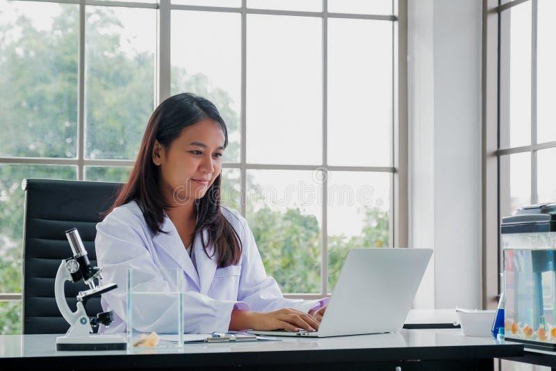 Kvinnlig doktor Sitting At Desk som arbetar på bärbara datorn arkivbild