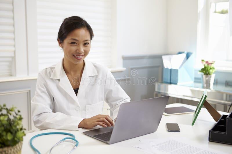 Kvinnlig doktor Sitting At Desk som i regeringsställning arbetar på bärbara datorn arkivfoton