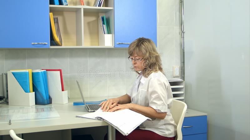 Kvinnlig doktor som använder bärbar datorsammanträde på skrivbordet i hennes kontor royaltyfri foto