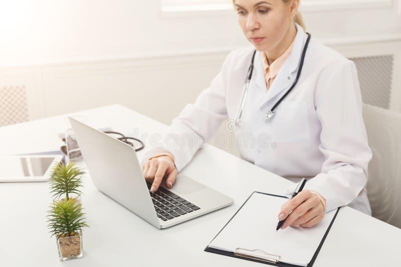 Kvinnlig doktor som använder bärbara datorn och skriver anmärkningar royaltyfri fotografi